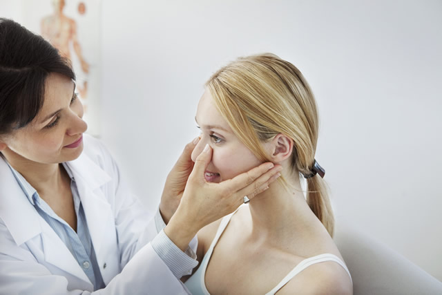 Cheek implants, woman having her face examined