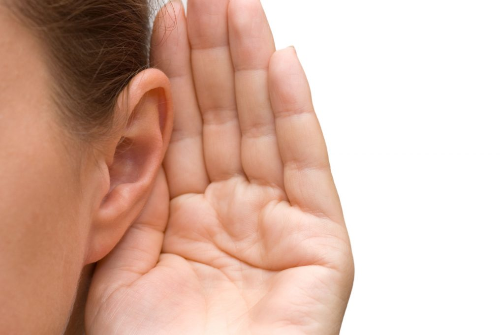 Woman trying to hear, hand held to ear - ear tubes