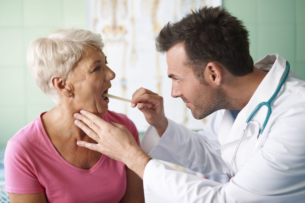Woman receiving throat evaluation