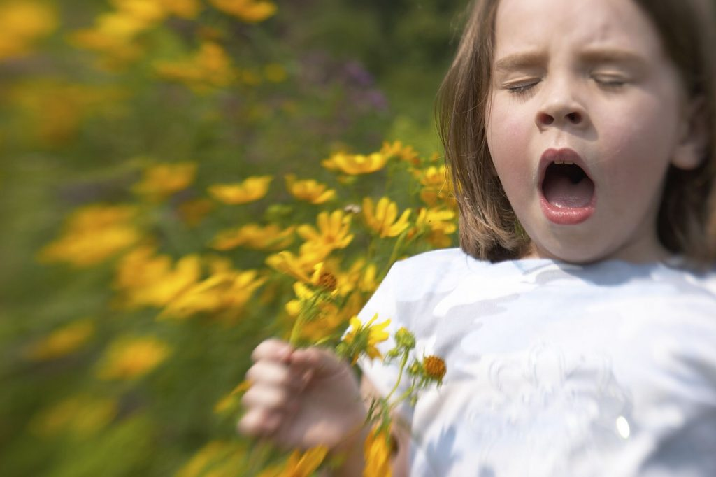 Young girl sneezing with flowers - Sinusitis