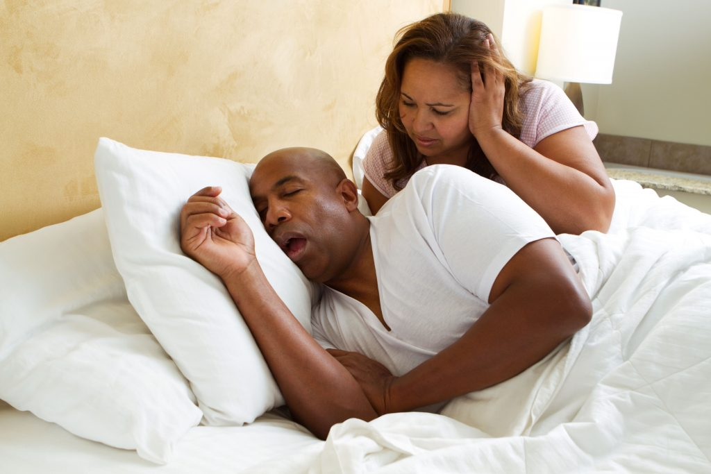 Man having trouble sleeping in bed - Sleep Apnea