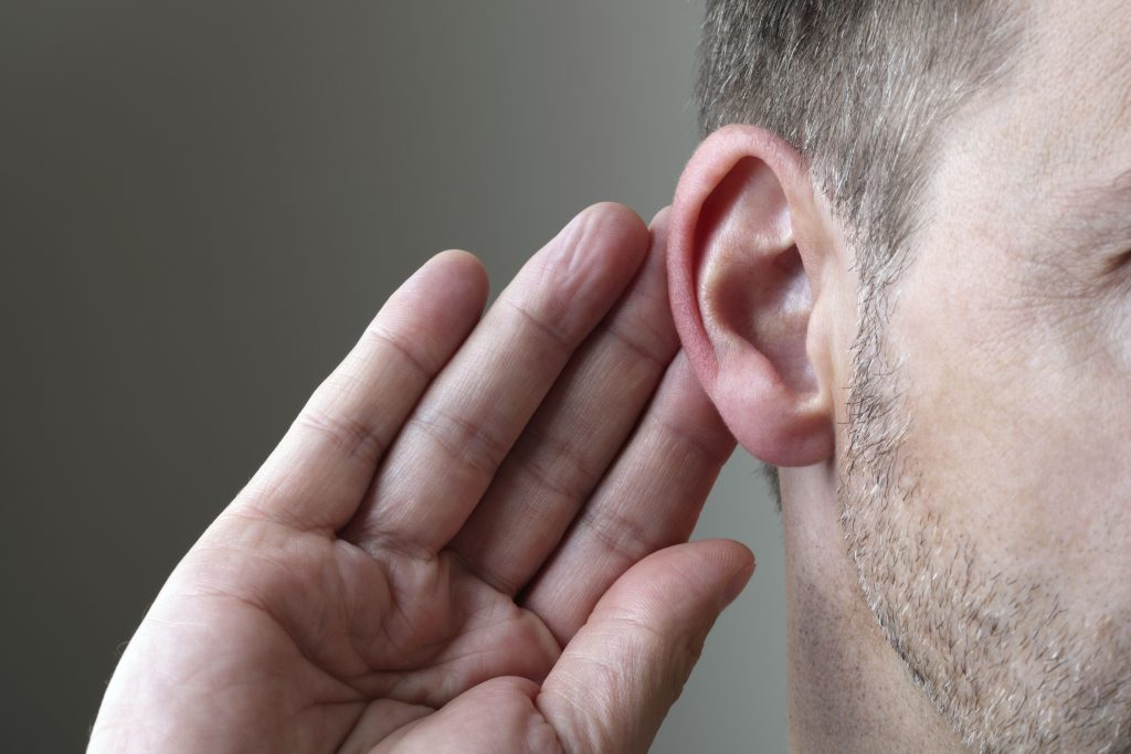Man holding hand up to ear - Sudden hearing loss