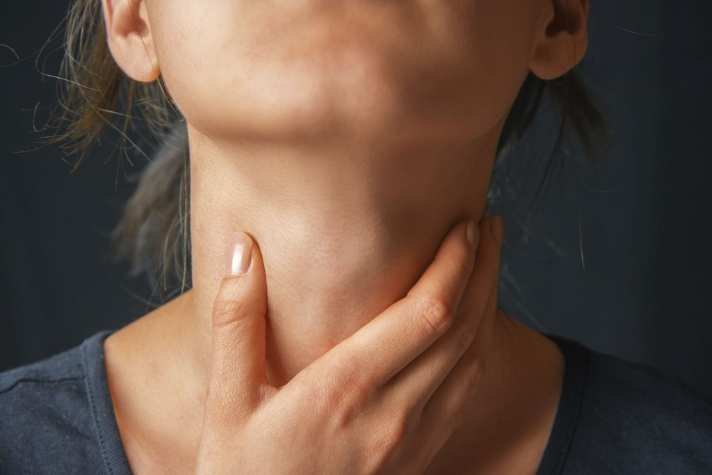 Woman with hand on throat - vocal fold paralysis