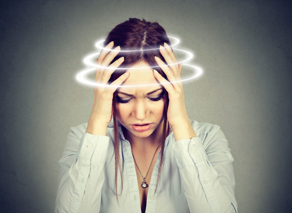 Woman holding her ears - vertigo treatment