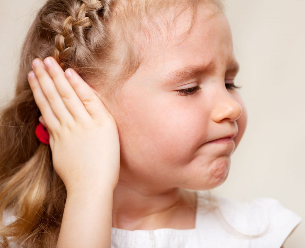 girl holding her ear - ear infection
